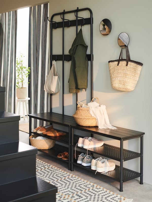 Un portemanteau et range-chaussures PINNIG à côté d'un autre banc rempli de chaussures. Deux miroirs sont accrochés au mur.