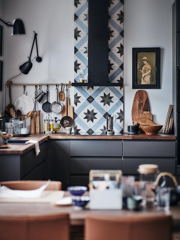 مطبخ حديث بواجهات VOXTORPرمادي داكن، مع سطح عمل خشبي وألواح واقية من الرذاذ لبلاطالمطبخ.