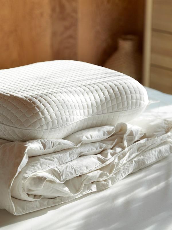 Piumino e cuscino ergonomico KLUBBSPORRE impilati su un letto con biancheria bianca in una stanza luminosa.