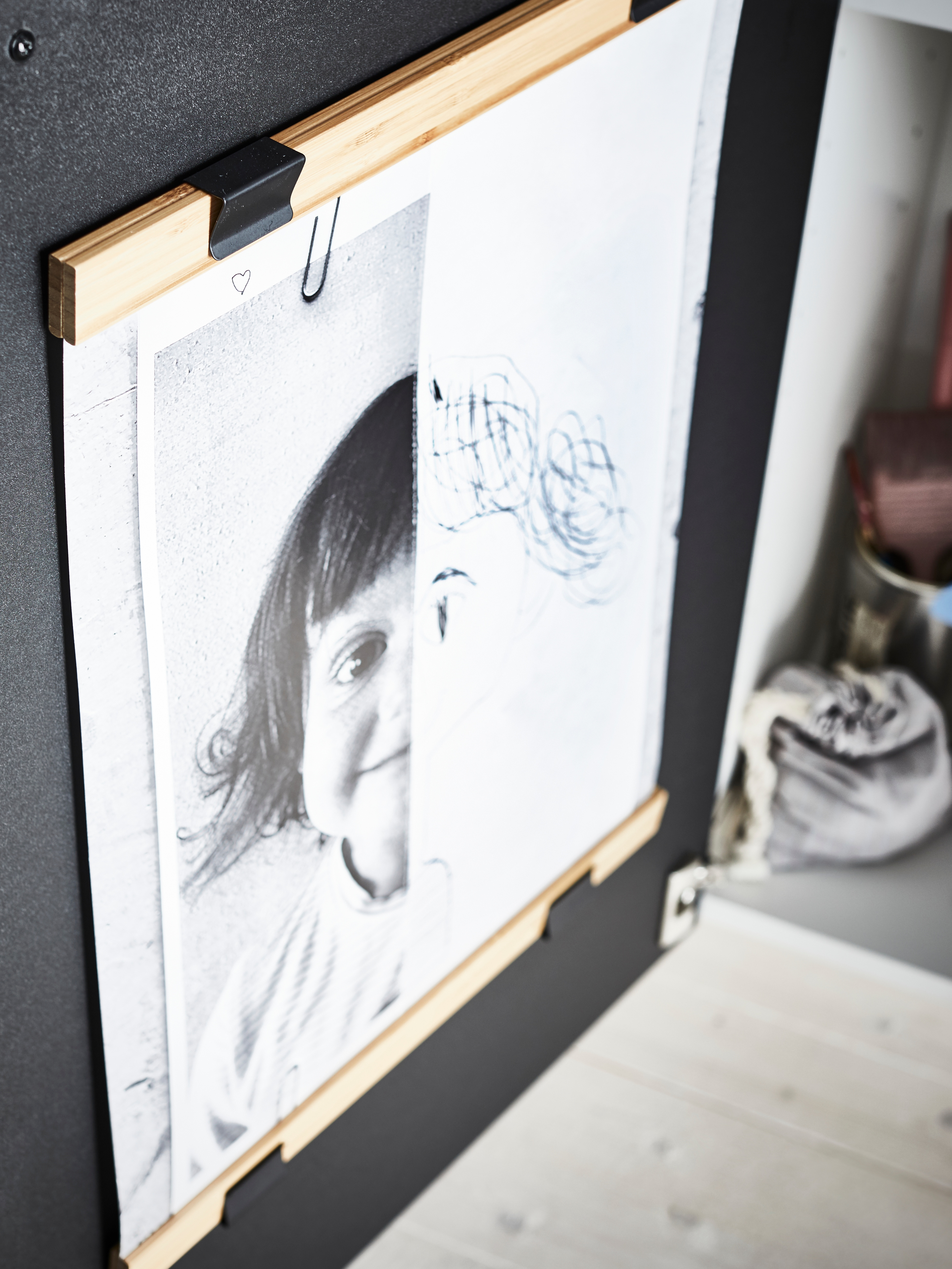 The inside of a kitchen cupboard door has two bamboo VISBÄCK poster hangers – one up, one down – framing a child's drawing.