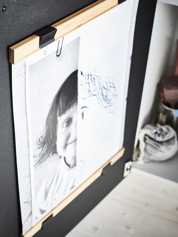 Keittiökaapin oven sisäpuolella on kaksi bambuista VISBÄCK-julisteripustinta, jotka kehystävät lapsen piirustusta. Toinen ripustin on kiinnitetty piirustuksen yläreunaan ja toinen alareunaan.