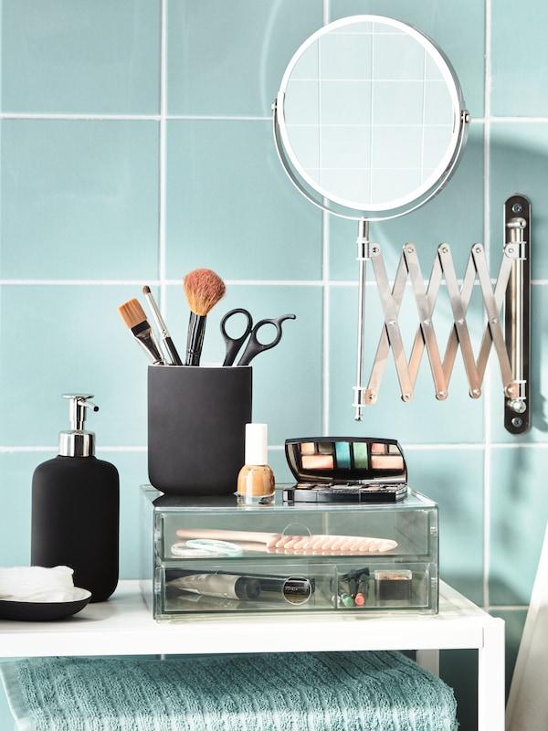 Et badeværelse med grønne fliser med et vægmonteret FRÄCK spejl oven over en GODMORGON minikommode fyldt med makeuptilbehør.