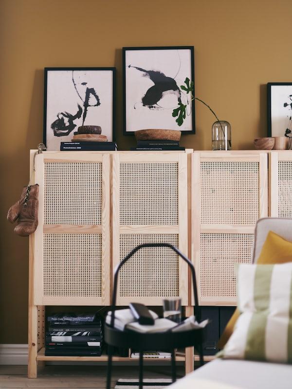 Des étagères IVAR avec portes bambou permettent de ranger des objets et d'en mettre d'autres en valeur, dans un espace de vie chaleureux et accueillant.