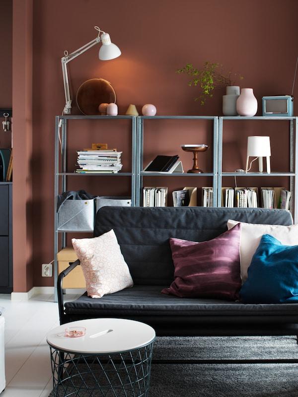 Litet vardagsrum med grå soffa och vinröda väggar.