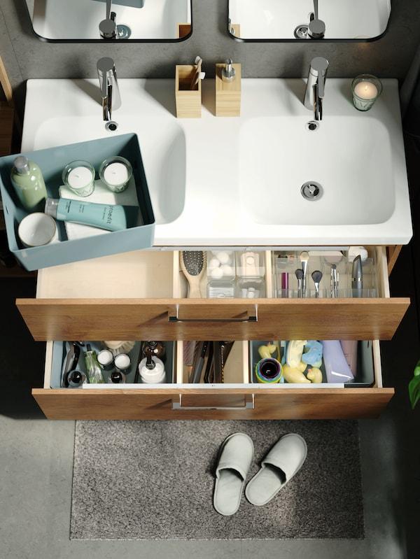أدراج مغسلة حمام مع صندوق بحجيرات GODMORGON داكن، وصناديق خضراء، وشمعة معطرة VÄLDOFT بكأس زجاجي أخضر فاتح.