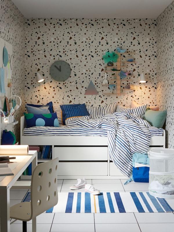 SLÄKT sängstomme med förvaring i vitt och SÅNGLÄRKA påslakanset  i ett barnrum.