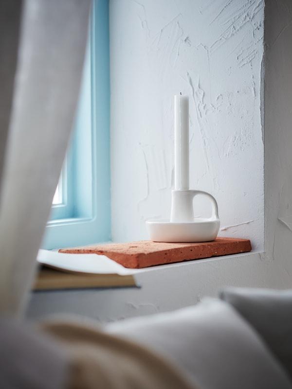 Portacandele bianco sulla mensola della finestra
