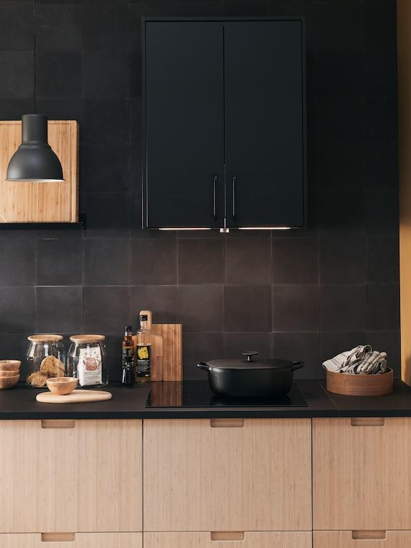 منطقة طهي بالمطبخ مع خزائنMETOD، ومصباح HEKTAR أسود وموقد طهي بالحث.