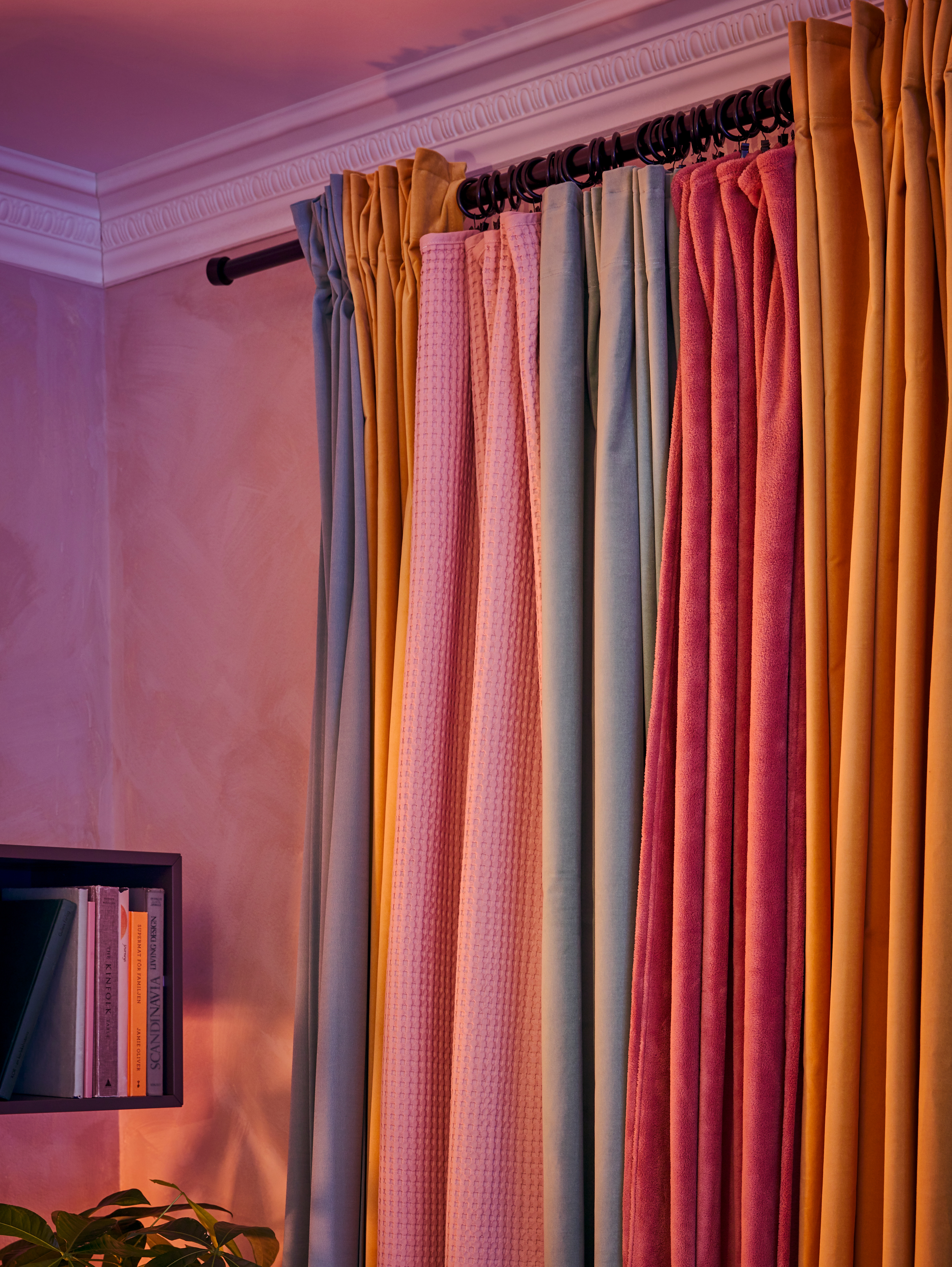 The curtains on a rod are pushed to the sides, and a dark pink TRATTVIVA bedspread hangs on curtain rings in the middle.