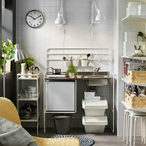 A white SUNNERSTA mini-kitchen with a fridge stands next to a white trolley. There are two work lamps on the wall.