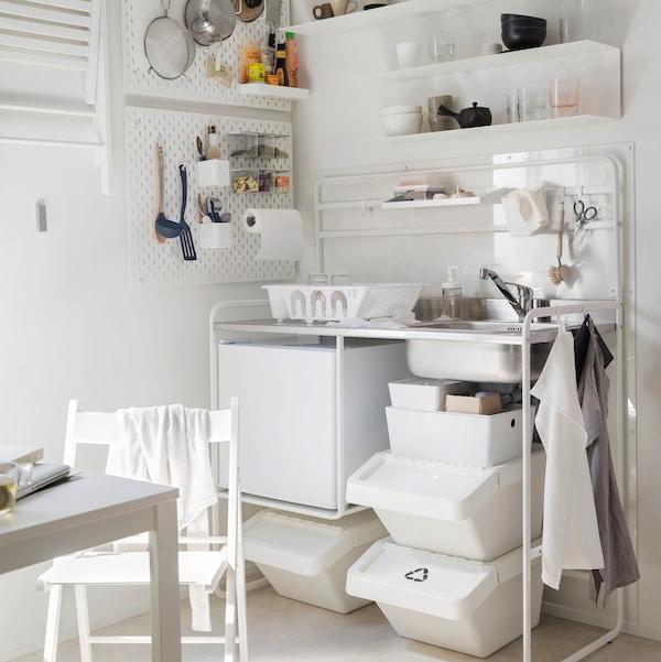 SUNNERSTA minikonyha egy erősen megvilágított helyiség sarkában, edényekkel és SKÅDIS falitáblára akasztott konyhai eszközökkel.
