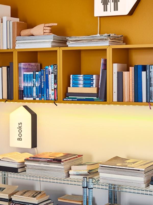 Mobili a giorno EKET gialli riempiti con libri e cassettiera in metallo a pavimento.