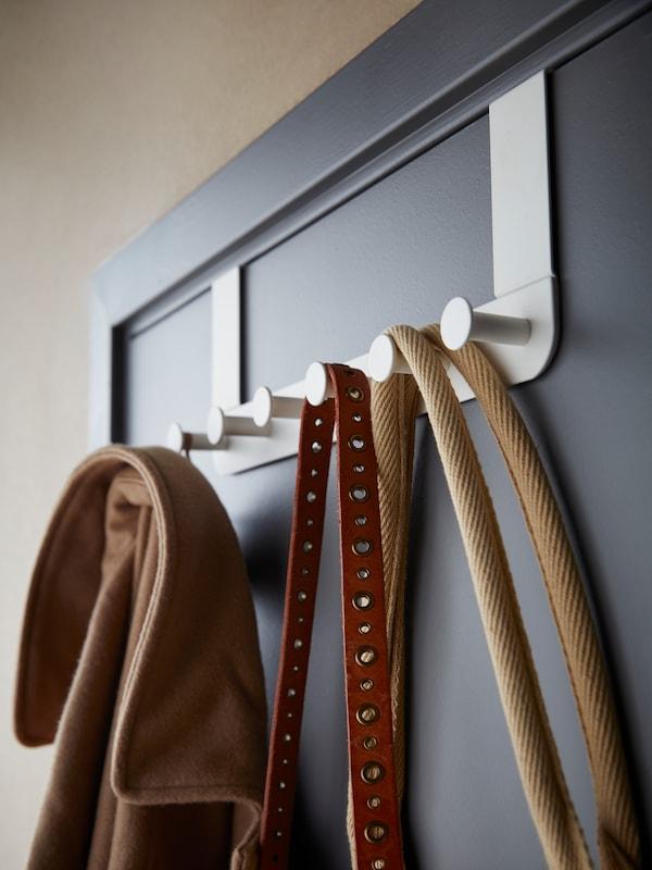 Белая и зеленая подушки висят на крючках на белой вешалке КУББИС, которая закреплена на розовой стене под подоконником.
