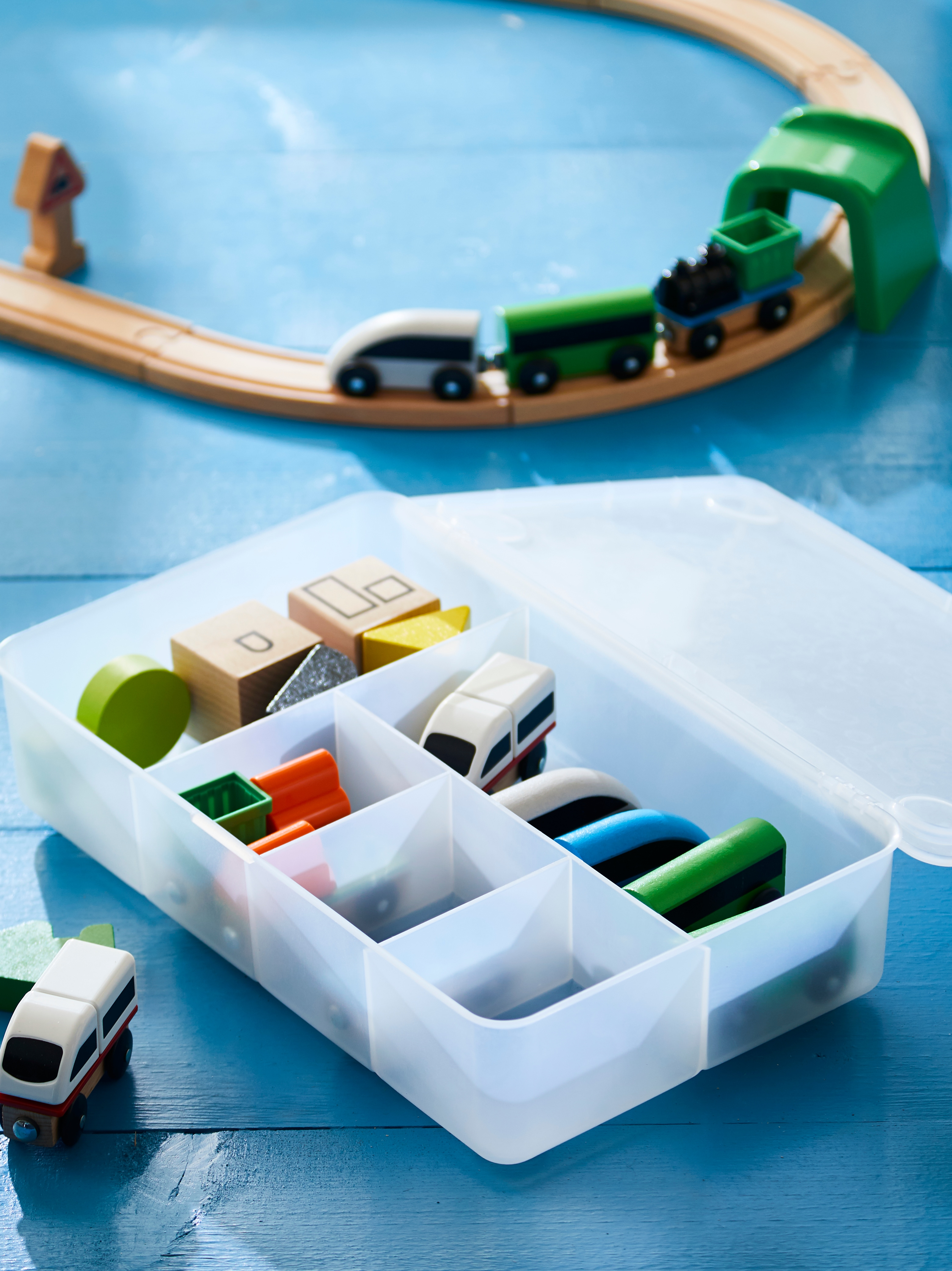 A LILLABO train set laid out on a blue floor with the pieces of the set organised in a GLIS transparent box.