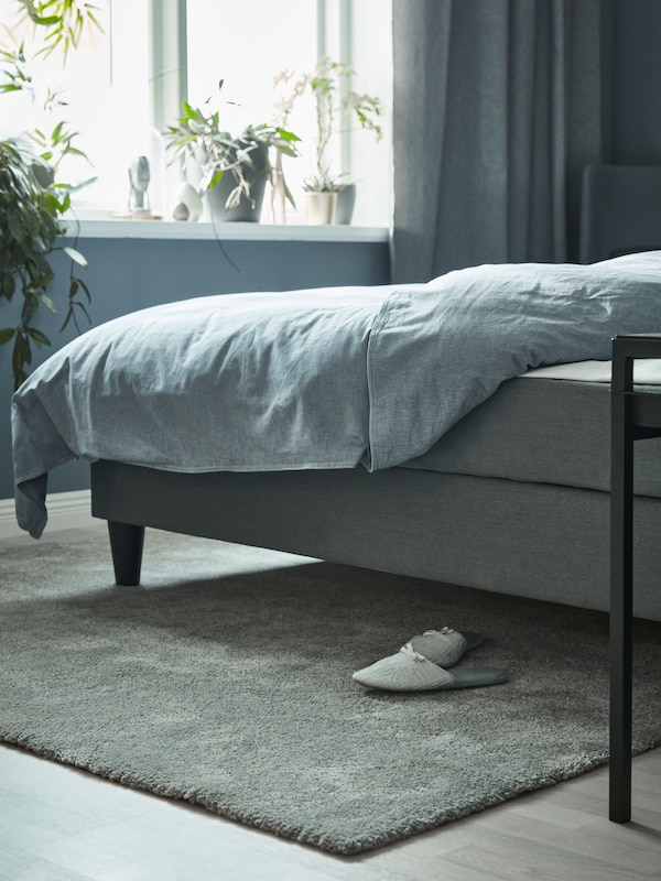 Un pat gri cu o pilotă albastru închis, un covor gri cu fire lungi, papuci de casă gri și plante pe un pervaz.