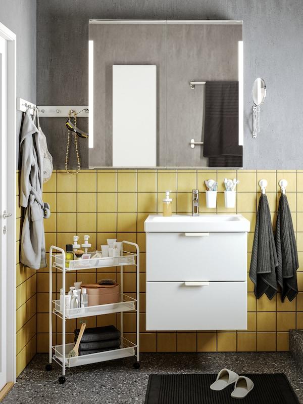 Bad med betongmønstrede grå vegger, gule fliser og et hvitt servantskap med to skuffer under et STORJORM speil.