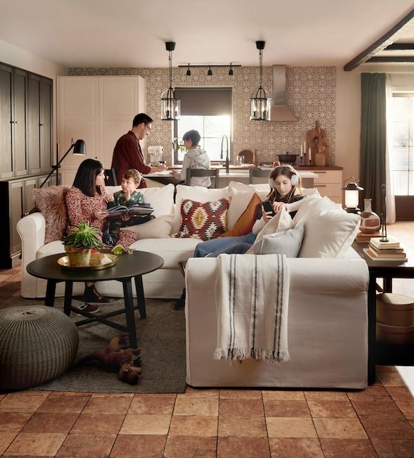 Obývací pokoj, maminka s dětmi sedí na pohovce, otec s dalším dítětem vzadu v kuchyni vaří.