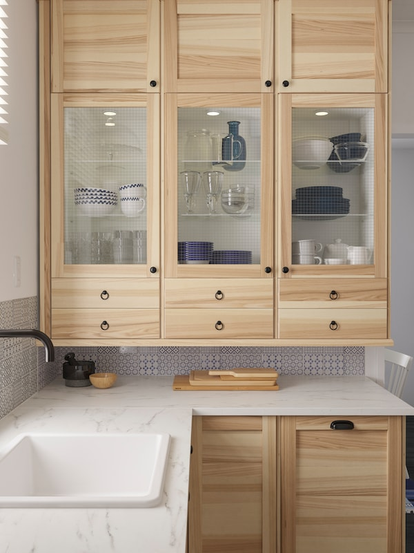 Six wall cabinets with three ash and glass TORHAMN doors that store tableware above a white marble-effect worktop.