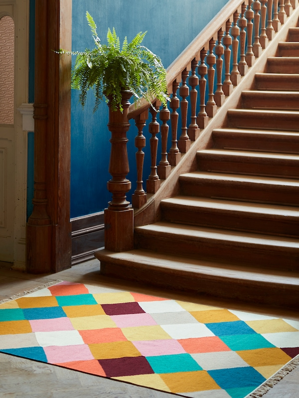 A colourful rug and the bottom of a flight of stairs with a wooden banister, a green plant, blue walls and a doorway.