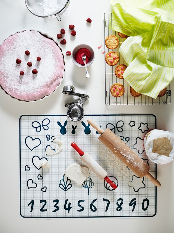 A bird's eye view of a baking stencil mat with rolling pins, near a pink pie decorated with raspberries.