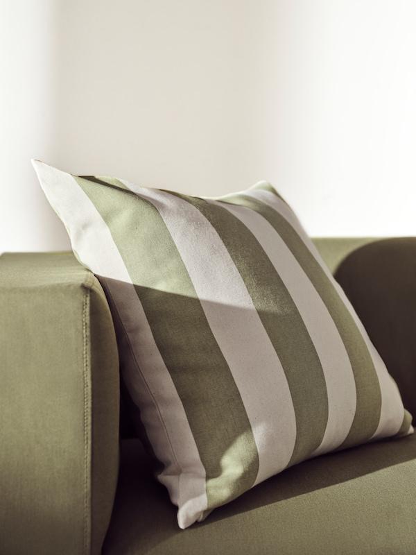 Vihreäraitainen HILDAMARIA-tyyny asetetaan vihreälle sohvalle lämpimässä auringonvalossa.