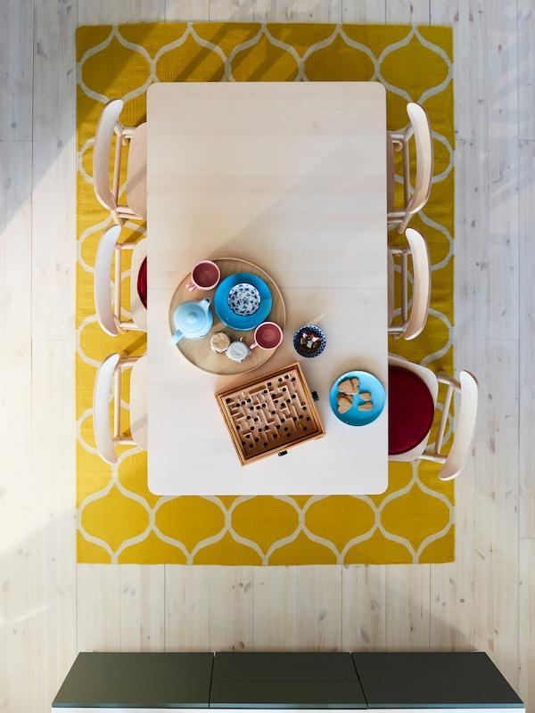 โต๊ะและเก้าอี้หกตัวทำจากไม้เบิร์ช วางอยู่บนพรมสีเหลืองมีลาย จัดไว้พร้องกาน้ำชาและแก้วมัคบนถาด