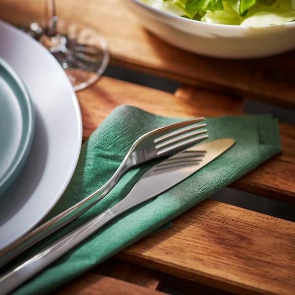 MOPSIG cutlery set on a FANTASTISK napkin on a wooden table.