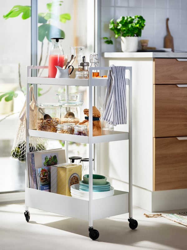 A white, sunlit NISSAFORS trolley loaded with food and accessories standing by a kitchen worktop and next to a glass door.