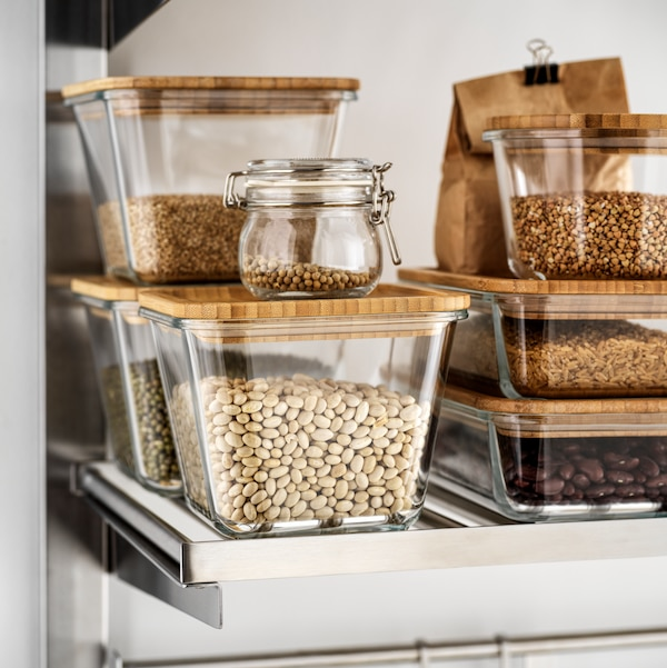 Several food containers in clear glass with bamboo lids filled with various dry foods standing on a shelf.