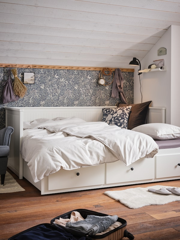 En hvid sovesofa med tre skuffer, et sengesæt med grå striber og en sort klemspot.