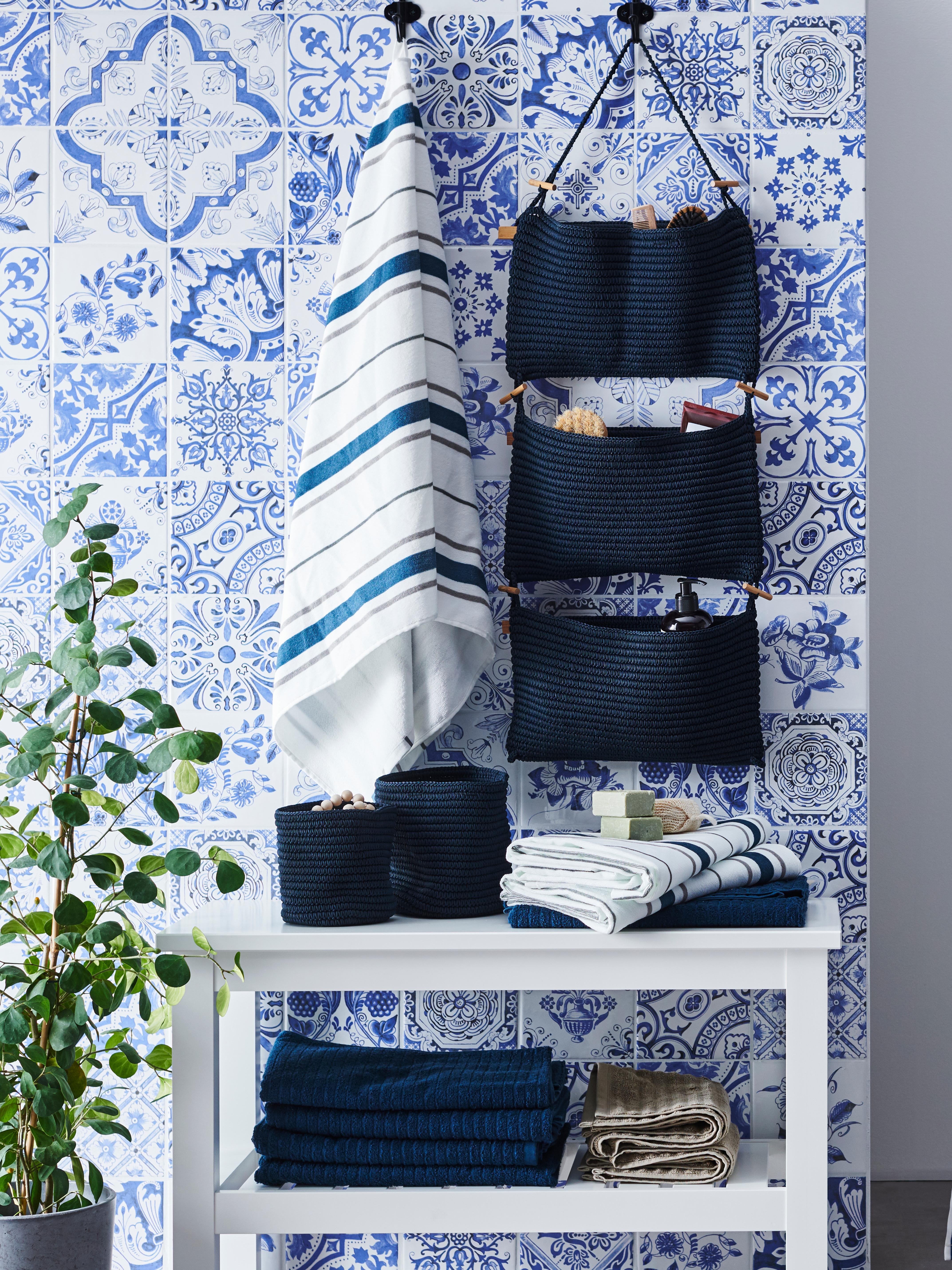 A blue NORDRANA hanging storage and an OTTSJÖN bath towel on a tiled bathroom wall with storage baskets underneath.