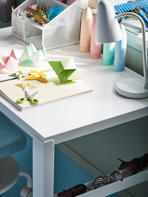 A children's desk with scissors, origami made from MÅLA paper in mixed colours and a white FUBBLA LED work lamp.