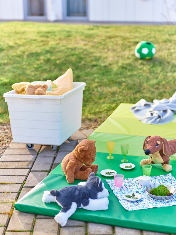 Playful dinner for a circle of soft-toy animals on a PLUFSIG mat by a patch of grass. A SOCKERBIT box with toys nearby.