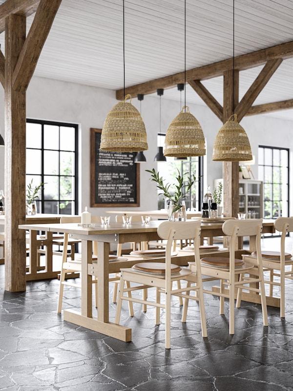 Sedie in legno e tavolo lungo in legno con tre lampade a sospensione con tre paralumi in pianta erbacea.