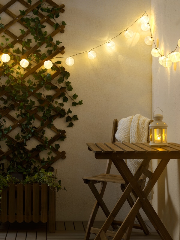 A wooden outdoor table and chair, a lantern on the table, hanging lighting, a wooden frame with greenery on the wall.