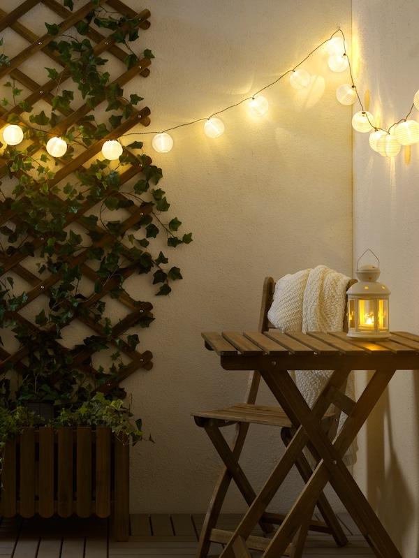 Une table et un fauteuil d'extérieur en bois, une lanterne sur la table, un éclairage suspendu, un cadre en bois avec de la verdure au mur.