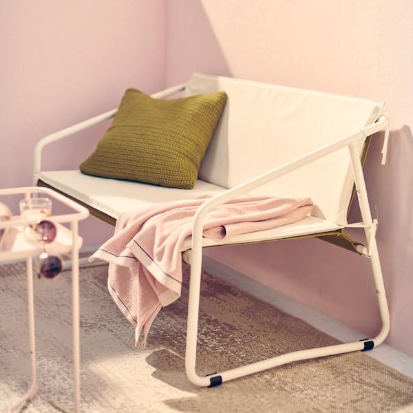 Ein weißes INGMARSÖ Gartensofa mit grünen Polstern und ein rosafarbenes Handtuch auf einem sonnigen Balkon in der Stadt.