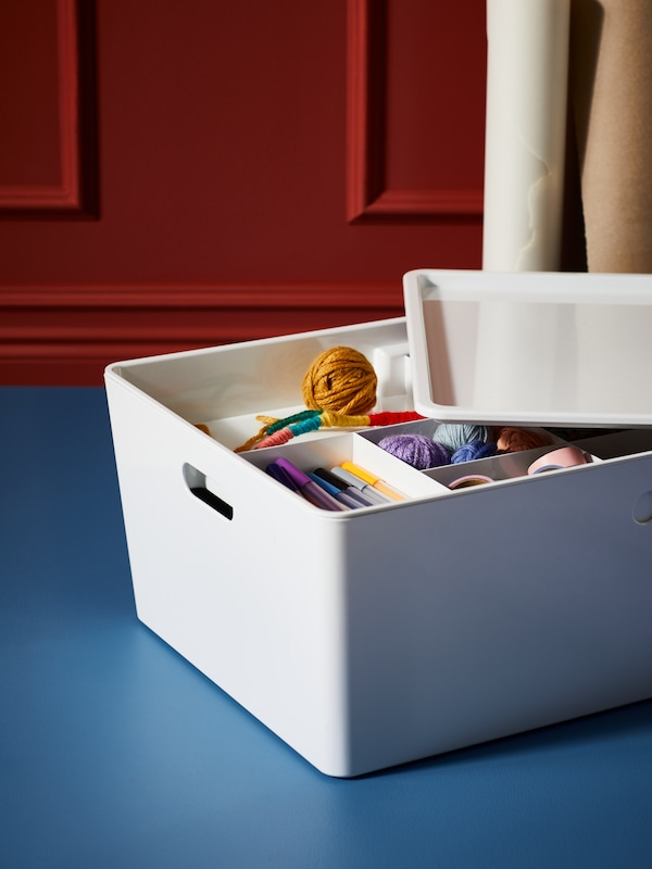 A KUGGIS box with lid, containing an assortment of sewing and crafting materials.