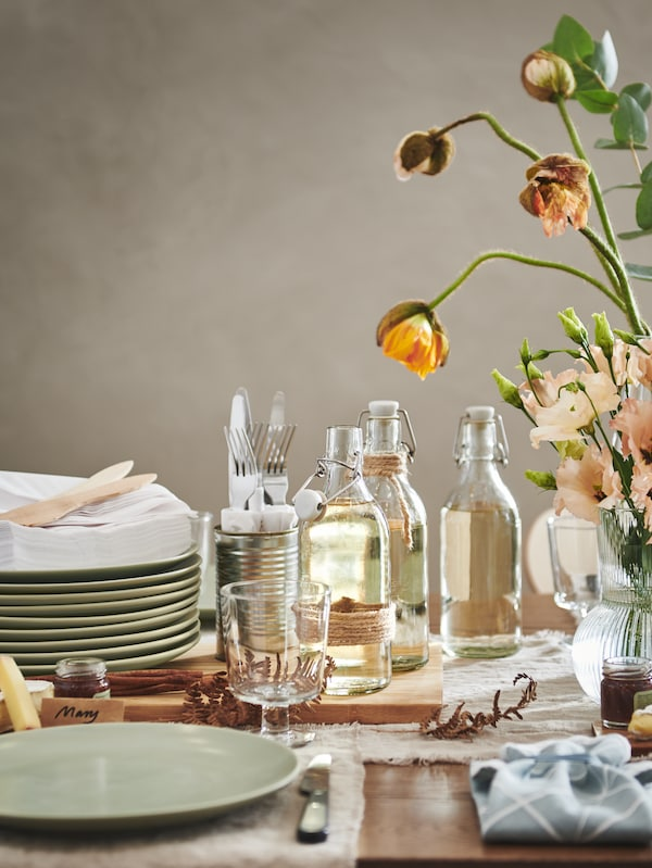 A section of a festively set table with stacked matt-green FÄRGKLAR plates, KORKEN bottles, IKEA 365+ goblets, and flowers.