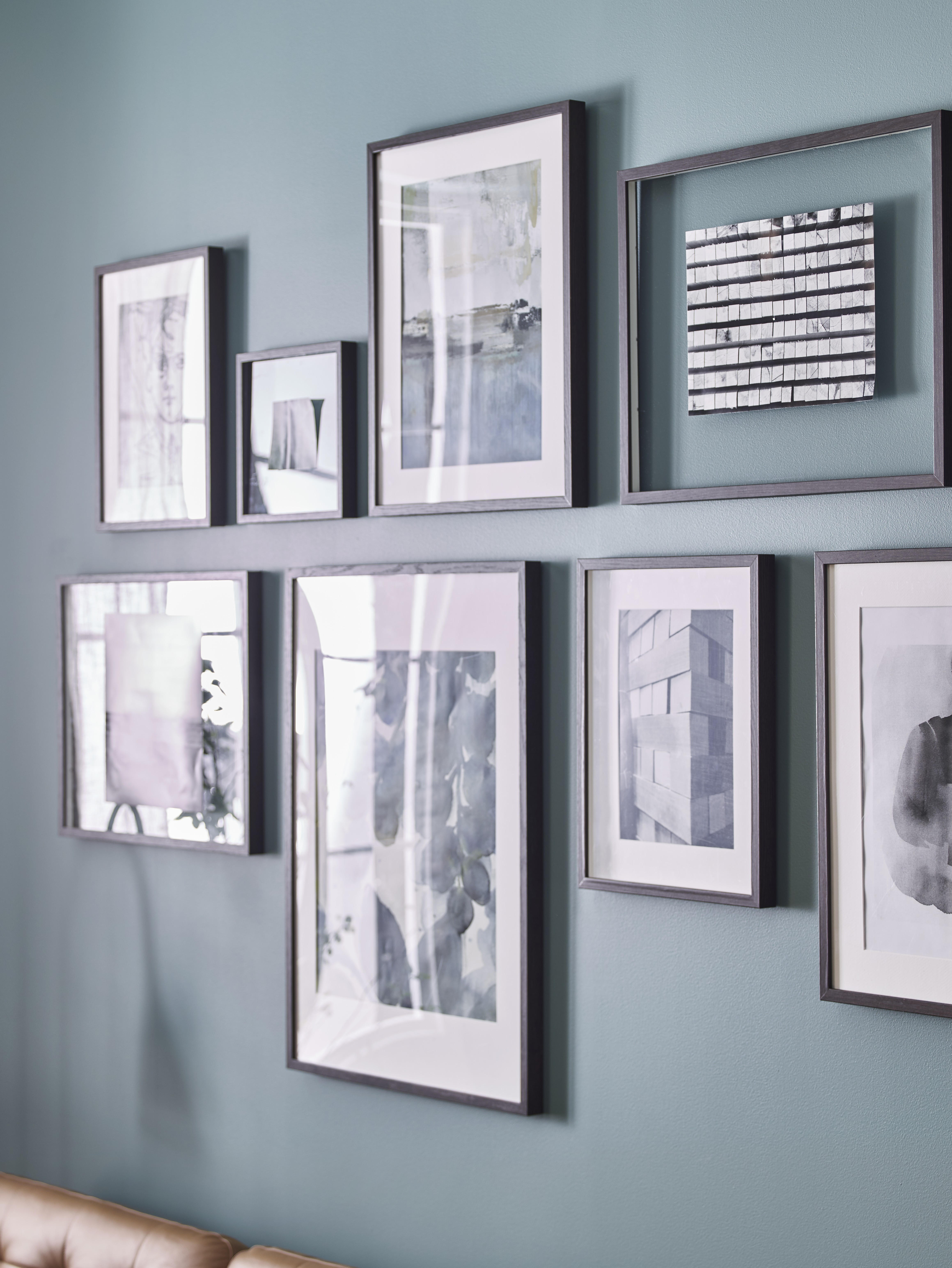 Various dark brown HOVSTA frames are arranged vertically and horizontally on a turquoise wall, displaying grayscale art.