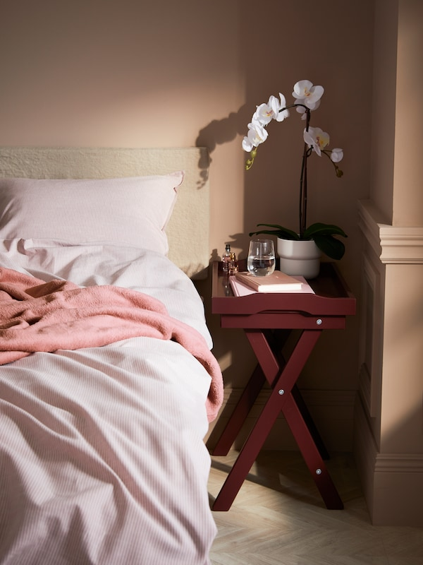 A bedroom with a pink duvet cover and a burgundy tray used as nightstand.