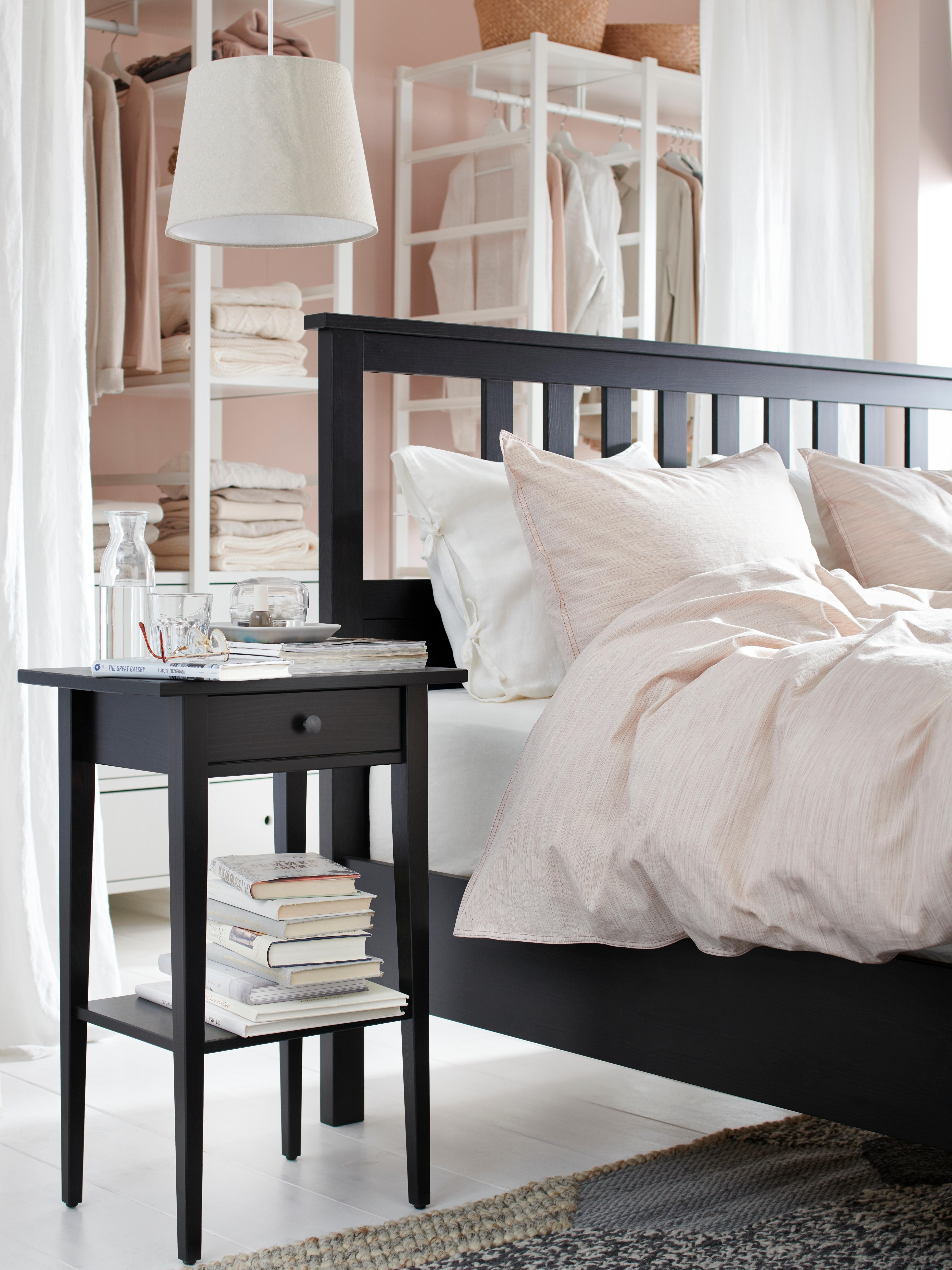 Crno-smeđi HEMNES okvir kreveta nalazi se ispred tri bijele jedinice za odlaganje pored crnog noćnog ormarića sa složenim knjigama.