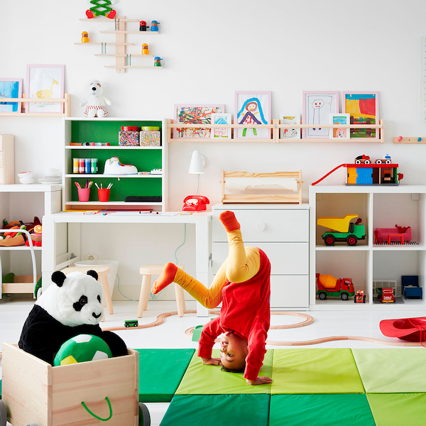 A child doing a somersault in a colourful room.