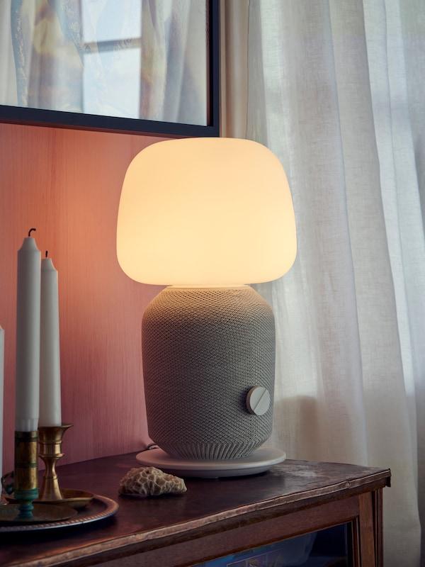 Lampada da tavolo SYMFONISK con cassa Wi-Fi integrata, vassoio giallo, cuffie e fotocamera su una cassettiera.