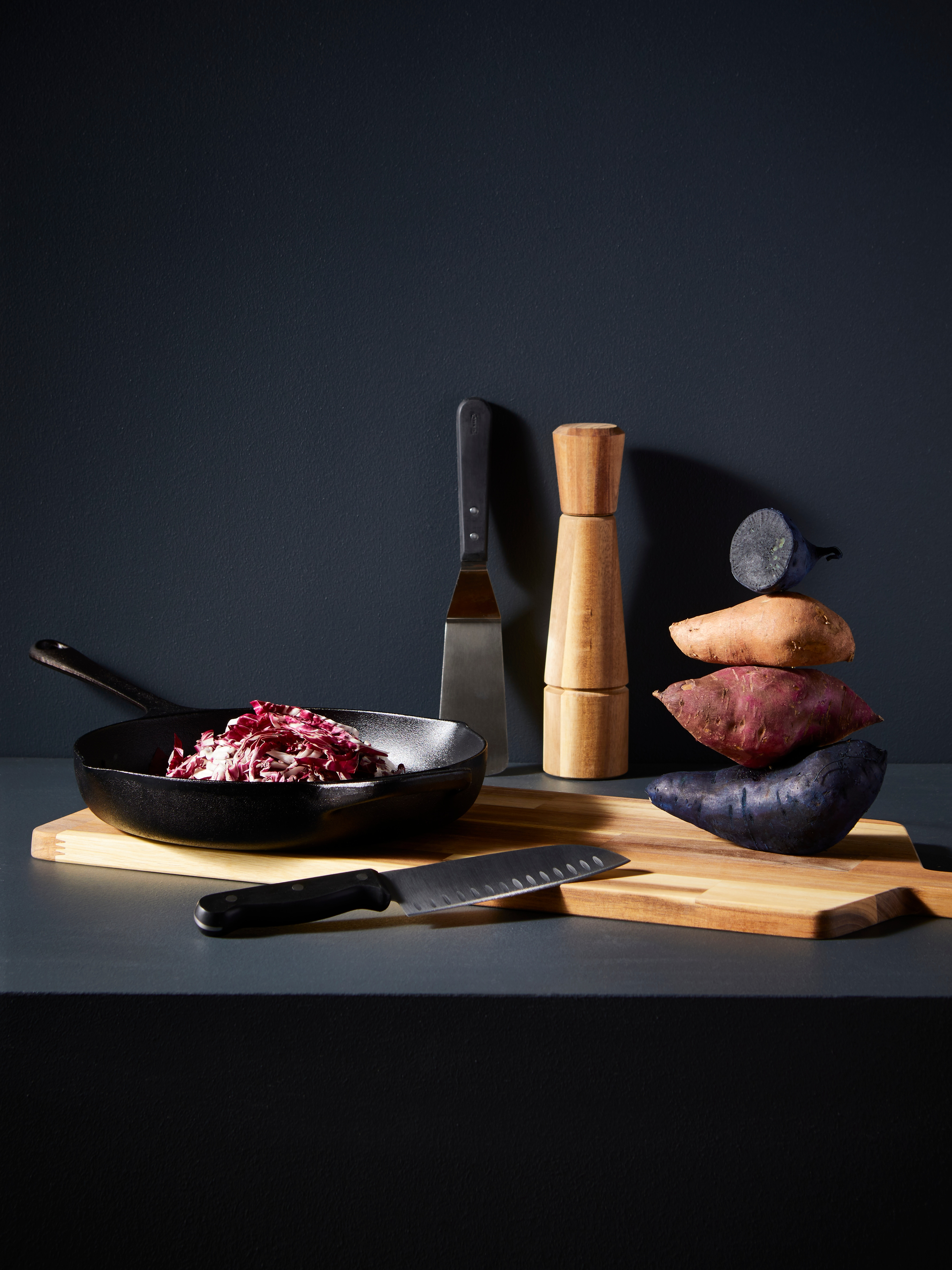 VARDAGEN cast iron frying pan, knife and spatula on a wooden board with potatoes stacked together and pepper mill.