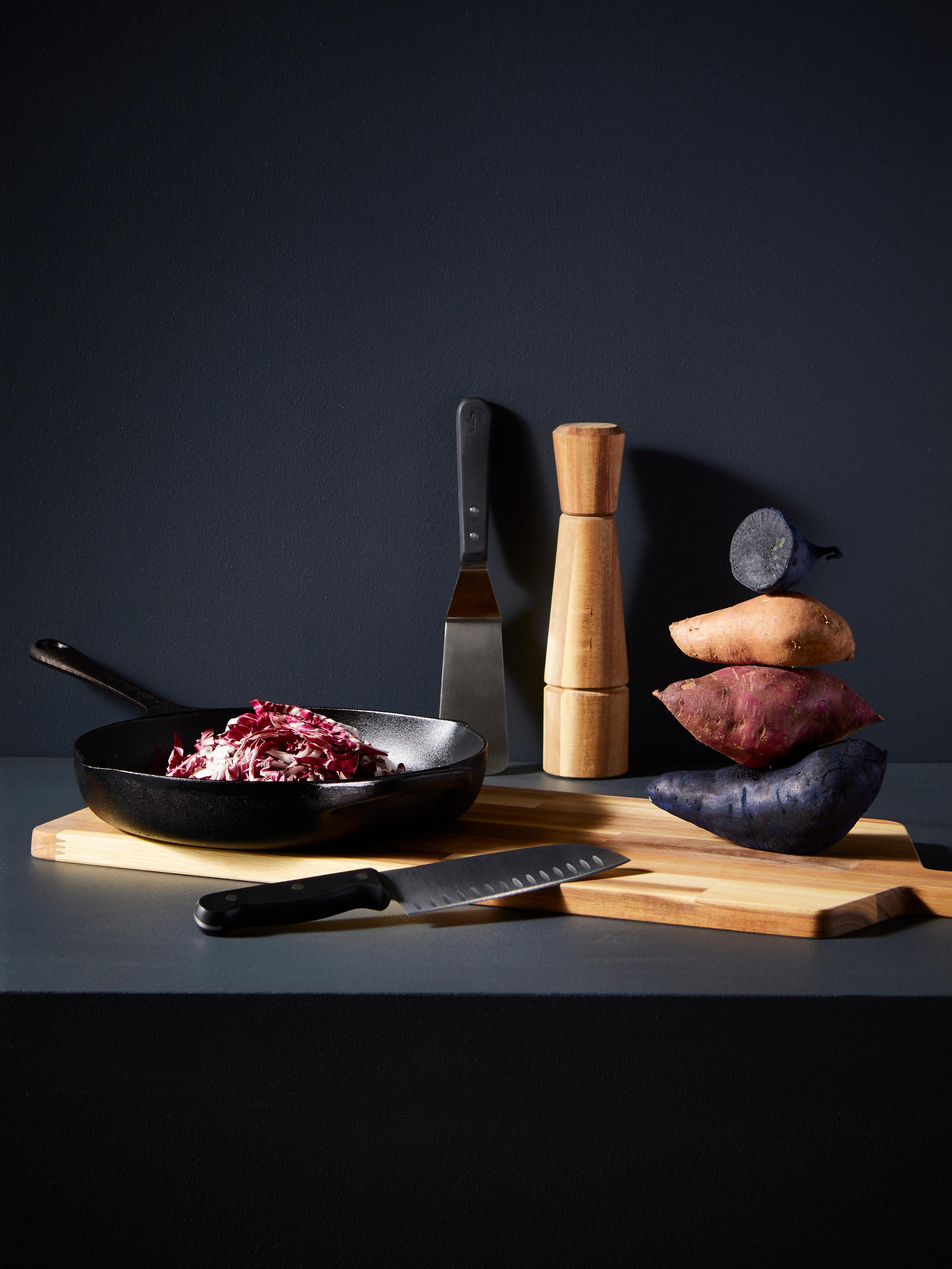Una padella, un coltello e una spatola sono poggiati su un tagliere di legno vicino a una pila di patate e a un macinapepe.