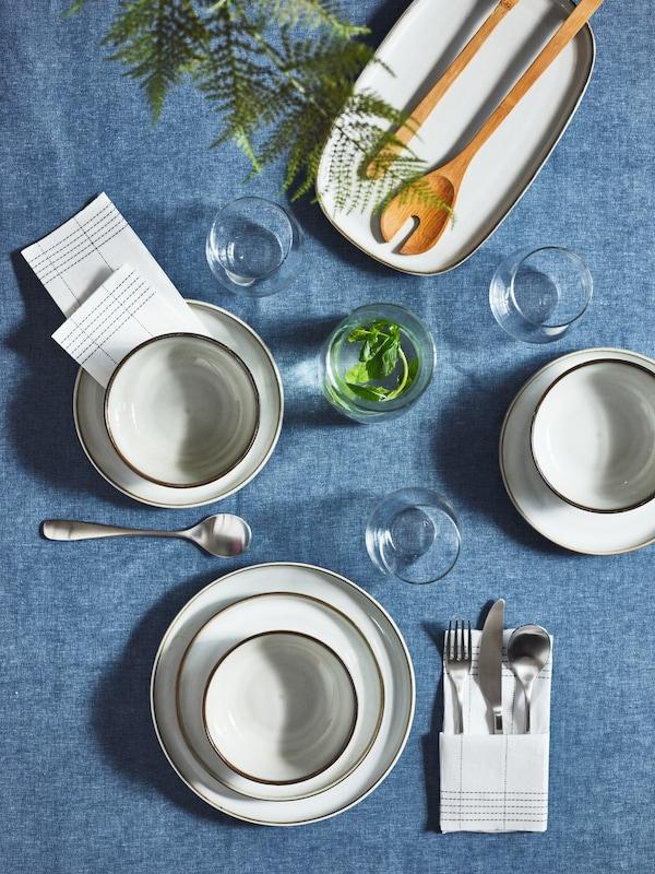 Detalle de una mesa adornada con platos y cuencos GLADELIG grises sobre un mantel SEVÄRD azul oscuro.