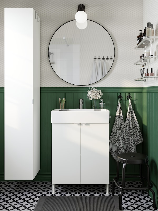 A black mirror hangs above a white wash-basin and two white cabinet doors in front of a green wall panel.