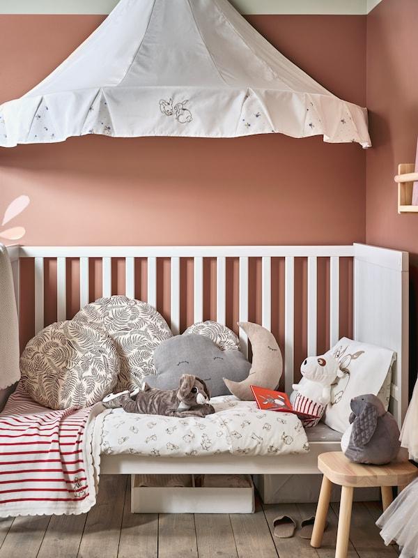 Valkoinen SUNDVIK-pinnasänky, johon on pedattu RÖDHAKE-vuodevaatteet, viltti ja tyynyjä, Sängyllä on pehmoleluja ja sängyn päällä on vuodekatos.