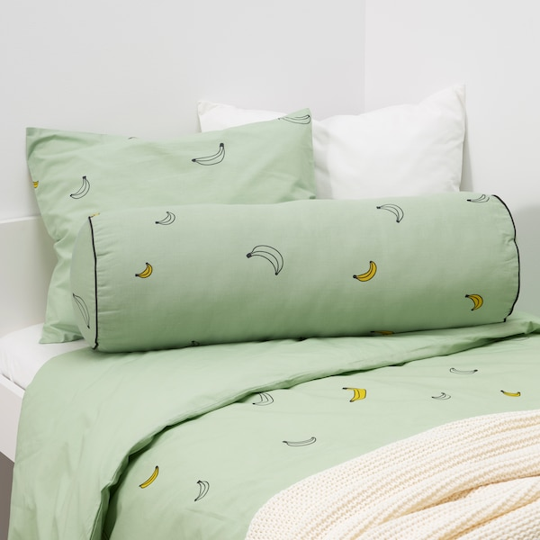 A pale green VÄNKRETS cushion with a banana pattern lies on a bed which has identical VÄNKRETS bed linen.